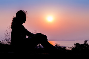 silhouette of a woman sitting at the clift during sunrise in national park