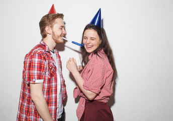 young cheeky guy and girl have fun, laughing in party caps with pipes, isolated over white