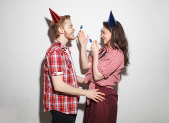 young modern cocky guy and girl have fun, laughing in party caps with pipes, isolated over white