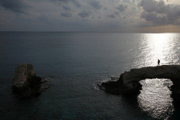 A man walks on a natural rock arch in Ayia Napa
