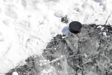 Hockey puck resting in a snowbank on the edge of a pond hockey rink