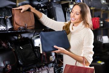 Happy female customer purchasing new hand bag