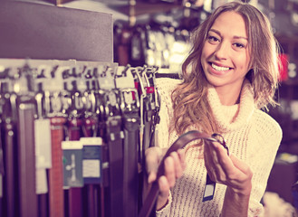 Positive woman buying leather belts at shop