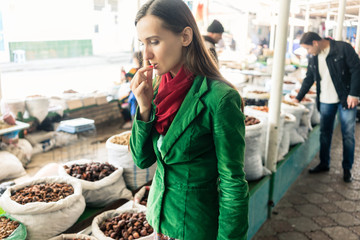 Beautiful woman tasting dried fruit on Central Asian bazaar