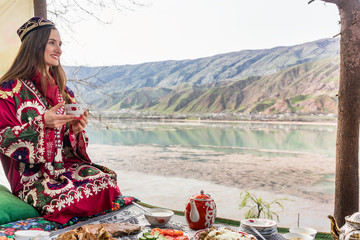 Tajik woman sitting in restaurant by the lake