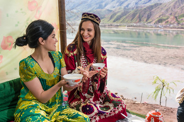 Two Tajik friends in traditional clothing eating lunch in restaurant