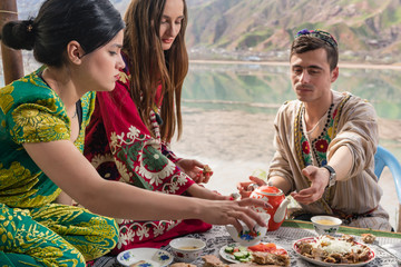 Group of Tajik women and men eating together in lakeside restaurant