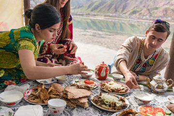 Women and man in traditional clothing of Tajikistan eating in restaurant by the lake