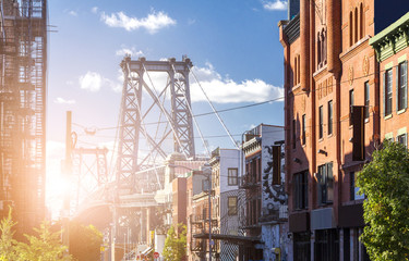 New York City street scene with sunlight shining on the Williamsburg Bridge in Brooklyn