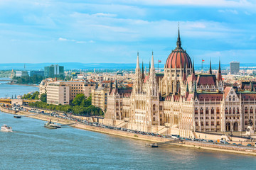 Travel and european tourism concept. Parliament and riverside in Budapest Hungary with sightseeing ships during summer day with blue sky and clouds Fototapete