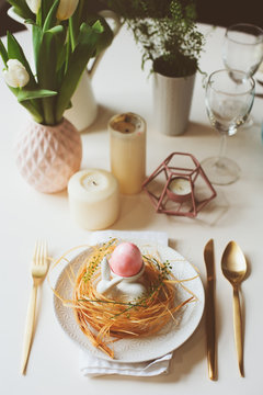 easter festive table details. Dining place decorated in pink and gold tones, with nest, bunny and eggs.