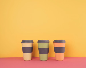 Take away coffee cups on colorful paper background. Recycling consept.