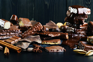 A variety of chocolate products on a dark background.