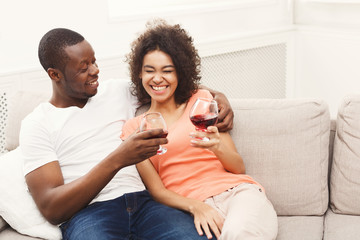 Smiling black couple drinking wine on sofa at home