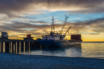 Small port, cargo ship and cranes on the sunset