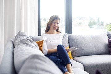 Smiling middle aged woman using digital tablet while relaxing on sofa at home.