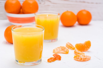 Mandarin juice in a glass and slices of tangerines on a white table