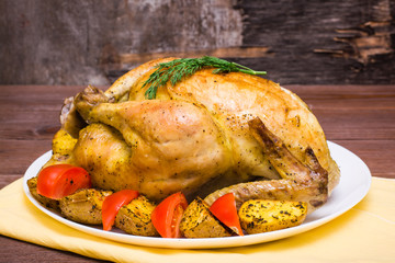 Baked whole chicken with a garnish of potatoes and tomatoes on a plate