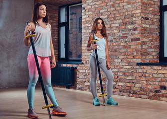 Women in sportswear hold a barbells.