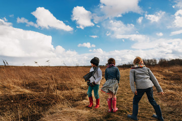 Three children standing in a rural landscape on a windy day