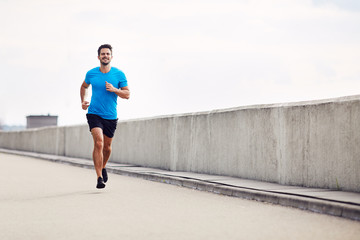 Handsome man running outdoors Wall mural