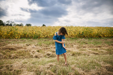Girl spinning in front of a soybean field