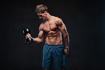 Athletic shirtless male biceps dumbbell workout.