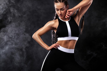 A strong athletic woman on black background wearing in black fashion sportswear, fitness and sport motivation. Sport concept with copy space.