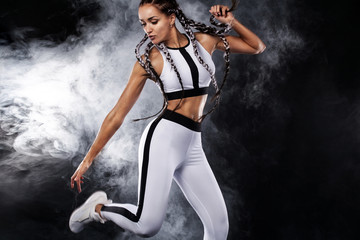 A strong athletic woman on black background wearing in white sportswear, fitness and sport...