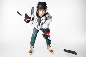 Young hockey player in safety gear with stick looking straight aggressively