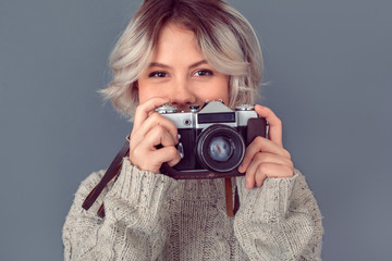 Young woman in a woolen sweater isolated on grey wall winter concept holding camera smiling