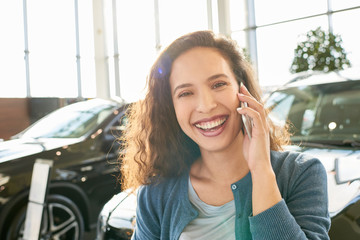 Head and shoulders portrait of cheerful curly woman posing for photography with charming smile while talking on smartphone, interior of modern car showroom on background