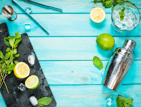 Mojito cocktail making. Mint, lime, glass, ice, ingredients and shaker on blue wood background . Top view
