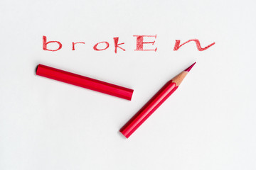 Broken two piece red pencil on white paper