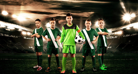 Kids - soccer champions. Boys in football sportswear on stadium with ball. Sport concept with soccer team.