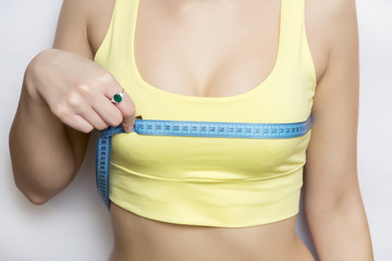 A picture of a young fit happy woman checking her breast measurement over white background