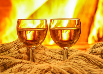 Two Glasses of white wine  and wool things near cozy fireplace, winter vacation.