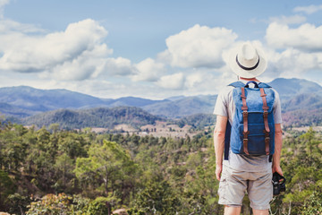 summer trekking in the mountains, tourist hiker travels outdoors, hipster with camera and backpack looking at panoramic landscape