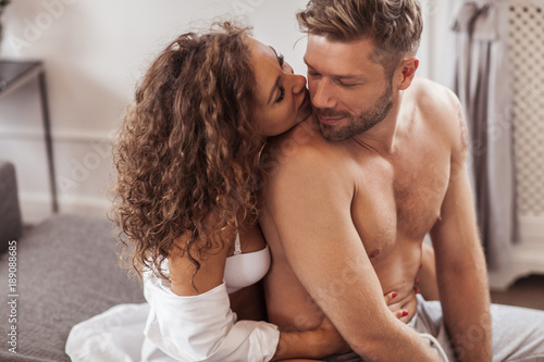lovely couple is kissing and hugging in the living room stock