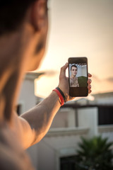 Over shoulder view of young man's hand holding smart phone and taking a selfie outdoors during sunset.