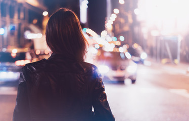 Fotomurales - Hipster girl in black leather jacket from back on background illumination glow bokeh light in night atmospheric city, hipster costs at a stop in headlights auto taxi; mockup glitter, lifestyle concept