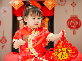 """Chinese baby girl  with traditional dressing up and """"FU"""" means """"lucky"""" greeting card.some """"FU"""" means """"lucky""""greeting card on the wall"""