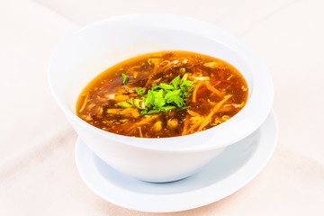 Chinese spicy and sour soup with chicken in white plate
