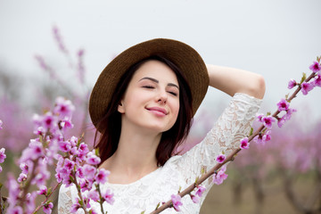 Young girl in hat near blossom peach tree