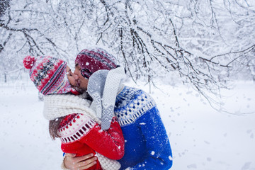Couple hugs and kisses in winter forest