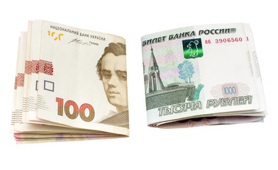 One hundred Ukrainian national currency hryvnia and one thousand rubles of Russian isolated on white background. Finance, international politics