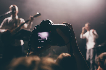 Someone's dslr camera with the video record mode on a concert with the live view picture on a screen. Music band on a stage as an object of shooting