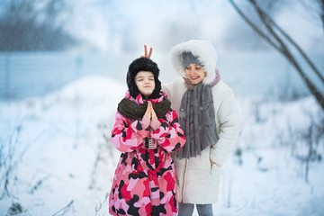 two little girls playing outdoors during strong snowfall. Active leisure with children in winter on cold days.