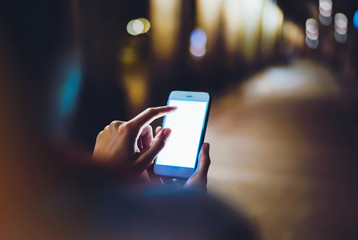 Woman pointing finger on blank screen smartphone on background bokeh light in night atmospheric city, hipster using in hands clean gadget mobile phone, mockup street, online wifi internet concept