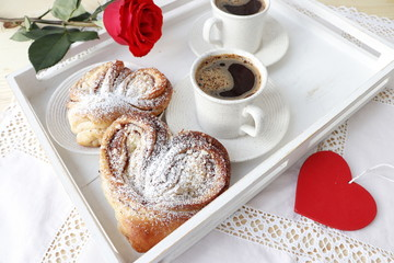 Valentine's Day. Breakfast for two, coffee and buns in the shape of heart. Selective focus.